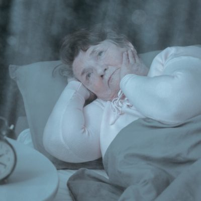 Older lady suffering from insomnia is trying to sleep